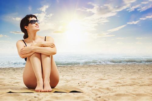 kobieta na plaży korzysta z kąpieli słonecznej